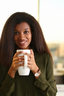 飲み物とカップを保持している笑顔の女性の肖像画