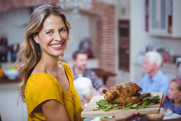 Портрет улыбается женщина, держащая разделочную доску с мясом