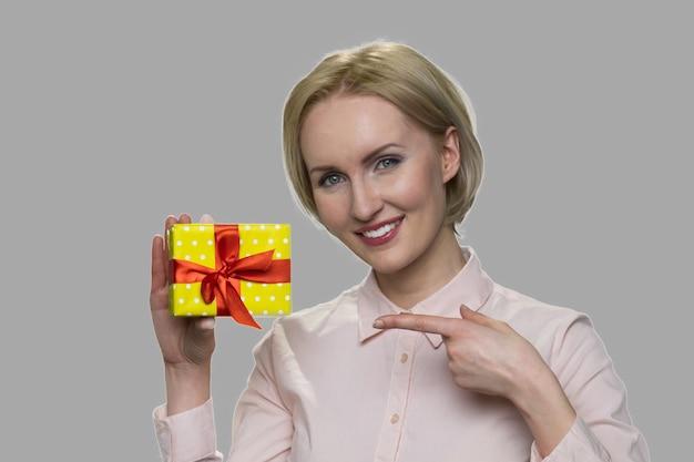 선물 상자를 들고 웃는 여자의 초상화입니다. 회색 바탕에 선물 상자를 보여주는 예쁜 비즈니스 아가씨. 계절 제안 개념.