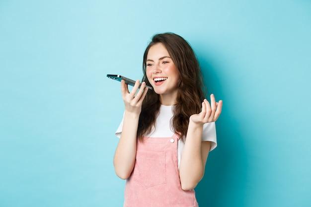 Портрет улыбающейся женщины, держащей телефон возле губ и говорящей, использующей переводчик приложений на смартфоне или записывающей голосовое сообщение, говорящей по громкой связи, стоящей на синем фоне