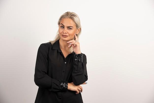 Портрет улыбающейся женщины в черной рубашке, позирующей на белом фоне. фото высокого качества