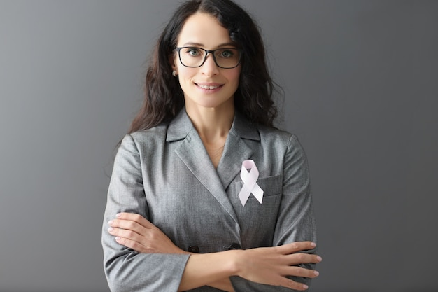 戦いのピンクのリボンのシンボルと彼女の胸に灰色のスーツを着て笑顔の女性の肖像画