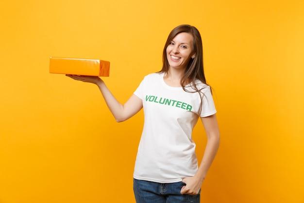 Портрет улыбающейся женщины в белой футболке с надписью зеленый заголовок волонтер держит оранжевую картонную коробку, изолированную на желтом фоне. добровольная бесплатная помощь, концепция благотворительности