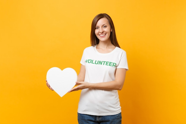Портрет улыбающейся женщины в белой футболке с письменной надписью зеленый титул волонтера держит белое сердце на желтом фоне. добровольная бесплатная помощь, концепция работы благотворительной благодати.