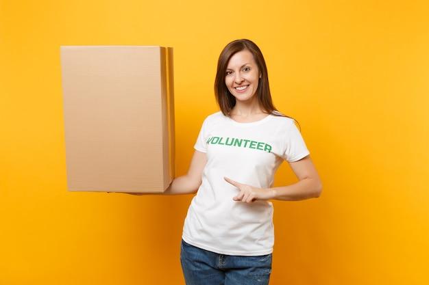 노란색 배경에 격리된 큰 판지 상자와 함께 녹색 제목 자원 봉사자라고 쓰여진 흰색 티셔츠를 입은 웃고 있는 여성의 초상화. 자발적인 무료 지원 도움, 자선 은혜 개념.