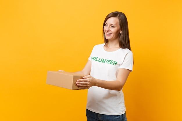노란색 배경에 격리된 빈 판지 상자와 함께 녹색 제목 자원 봉사자라고 쓰여진 흰색 티셔츠를 입은 웃고 있는 여성의 초상화. 자발적인 무료 지원 도움, 자선 은혜 개념.