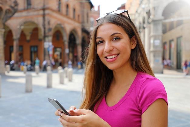 Портрет улыбающейся женщины, смотрящей в камеру и использующей смартфон в старом средневековом городе