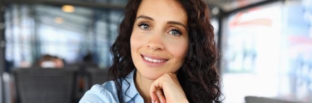 Портрет улыбающейся женщины, смотрящей в камеру с счастьем и радостью.