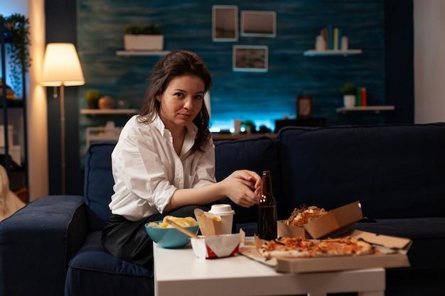 Портрет улыбающейся женщины, смотрящей в камеру, сидя на диване, наслаждаясь свободным временем