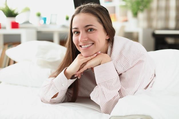 白いベッドの上の笑顔の女性の肖像画