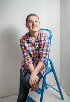 白い部屋で金属の脚立に座っている笑顔の女性の肖像画