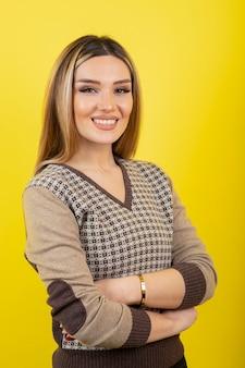 노란 벽에 팔짱을 끼고 서 있는 웃고 있는 여성의 초상화.