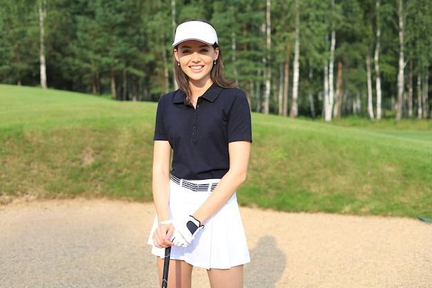 ゴルフコースでゴルフクラブと立っている笑顔の女性の肖像画