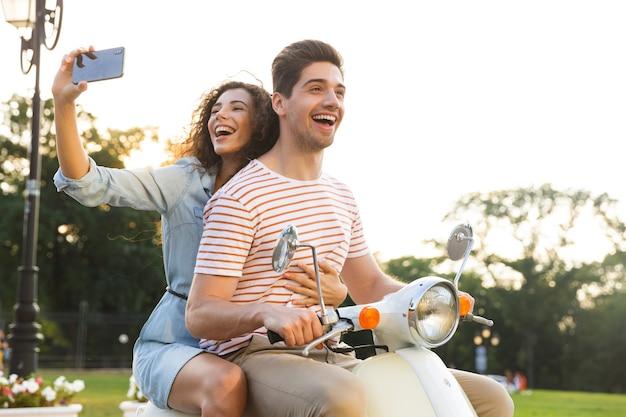 그녀의 남자 친구와 함께 도시 거리를 통해 오토바이를 타고있는 동안 스마트 폰에 셀카를 복용 웃는 여자의 초상화