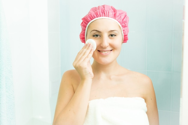 샤워 후 얼굴 크림을 사용하여 웃는 여자의 초상화