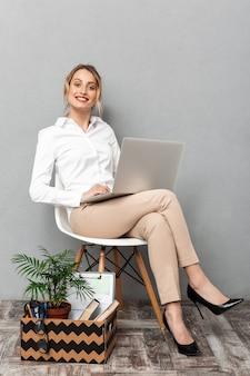 分離されたオフィス用品と椅子に座ってラップトップを使用して笑顔の女性の肖像画