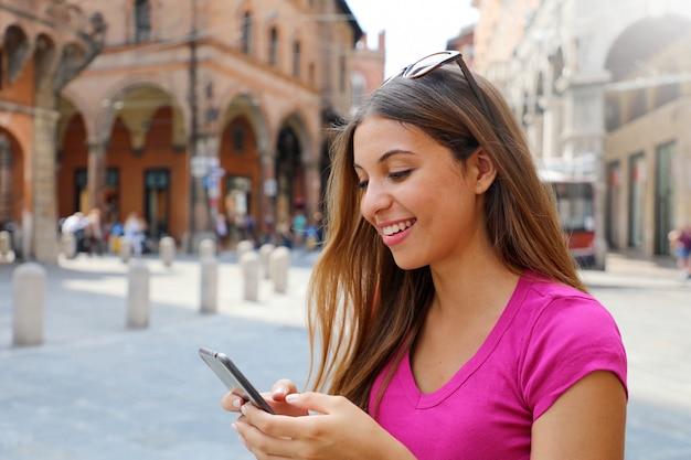 Портрет улыбающейся женщины, использующей смартфон в старом средневековом городе