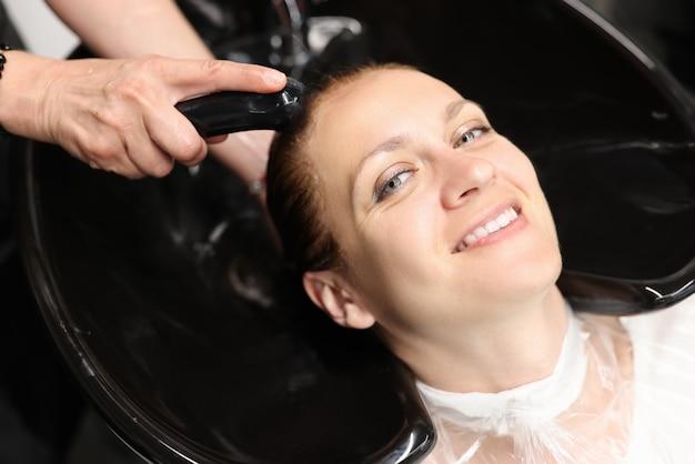 Портрет улыбающейся женщины, моющей волосы в раковине в салоне красоты