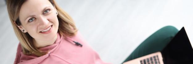 Портрет улыбающейся женщины с ноутбуком на ногах дистанционное образование и онлайн-курсы