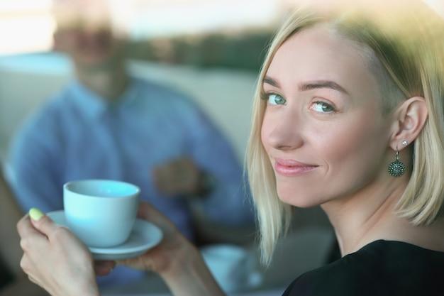 カフェでの会議でカップと笑顔の女性の肖像画