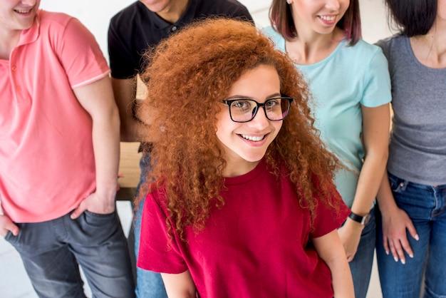 彼女の友人の前に立っている巻き毛を持つ笑顔の女性の肖像画