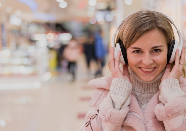 Портрет улыбается женщина с heaphones в торговом центре