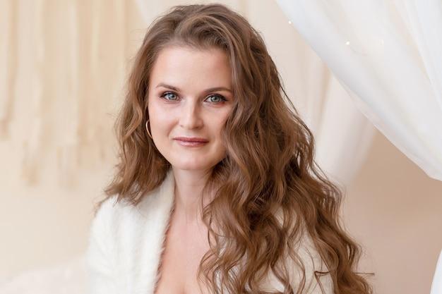 Портрет улыбающейся женщины с длинными волосами в бежевой спальне