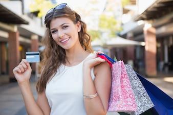 ショッピングモールでカメラを見てショッピングバッグとクレジットカードで笑顔の女性の肖像画