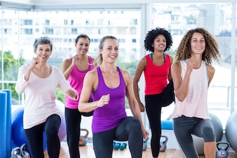 Portrait of smiling women exercising with clasped hands