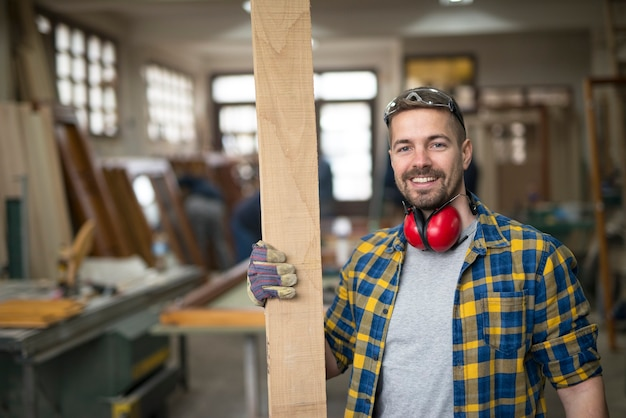 Портрет улыбающегося работника столярной мастерской, держащего доску древесного материала