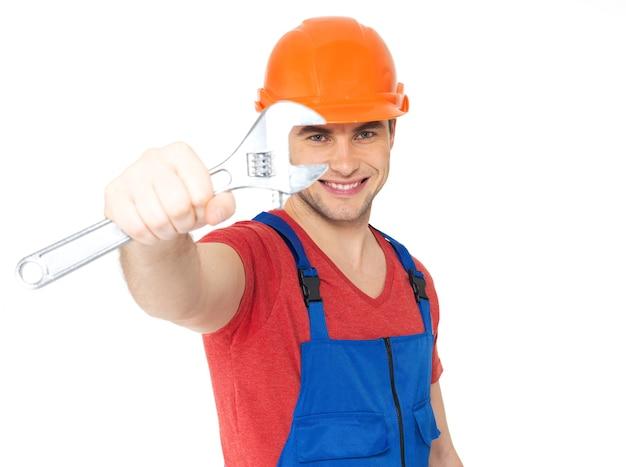 Портрет улыбающегося работника с большим гаечным ключом, изолированного на белом