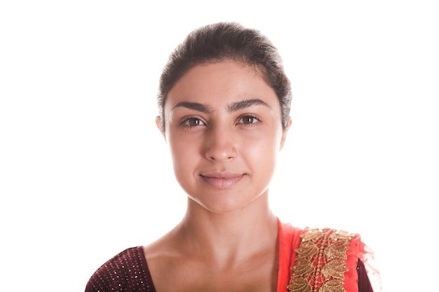 Портрет улыбающейся молодой взрослой индийской женщины в красном сари, изолированной на белом фоне