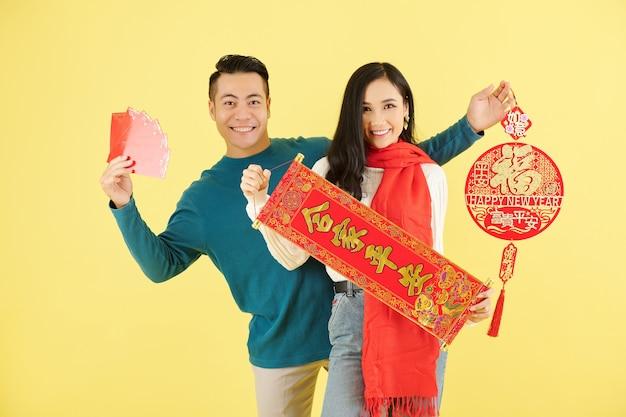 Портрет улыбающегося молодого азиатского парня и девушки, показывающих китайские украшения с наилучшими пожеланиями в наступающем году.