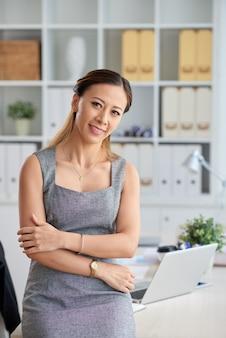 노트북으로 사무실 테이블에 기대어 다른 팔의 팔꿈치를 잡고 공식적인 드레스에 웃는 젊은 아시아 비즈니스 레이디의 초상화