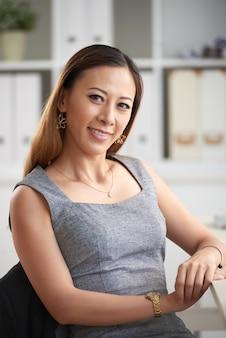 オフィスのフォルダーと棚に座って金のイヤリングで笑顔の若いアジアの女性ビジネスエグゼクティブの肖像画