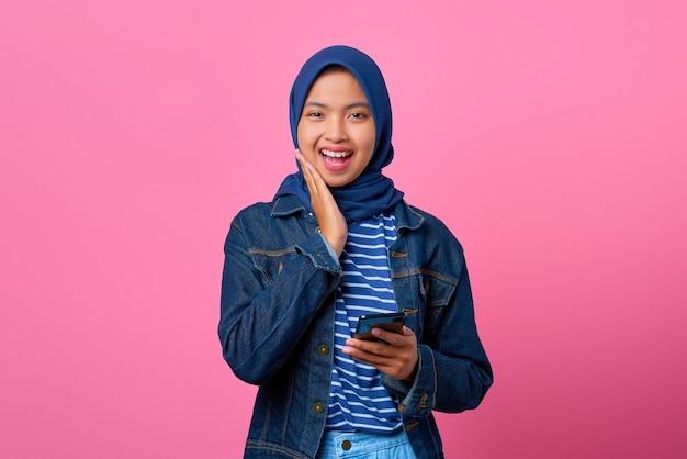 彼女の頬に手で携帯電話を保持している笑顔の若いアジアの女性の肖像画