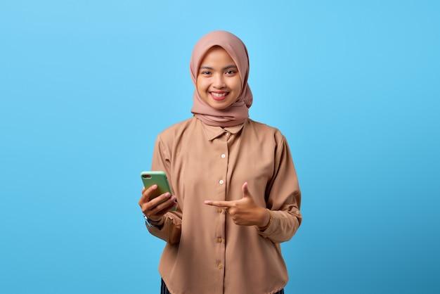指で携帯電話を指している笑顔の若いアジアの女性の肖像画