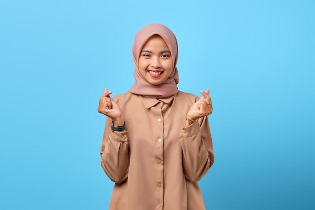 青い背景の上に指ハートを示す笑顔の若いアジアの女性の肖像画