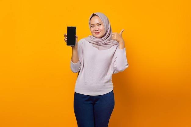 スマートフォンの空白の画面を表示し、親指を立てるサインを作る笑顔の若いアジアの女性の肖像画