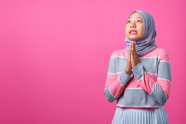 ピンクの背景に謝罪の表情で立っている笑顔の若いアジアの女性の肖像画