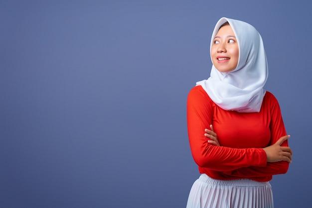 手を組んで立って見上げる笑顔の若いアジアの女性の肖像画