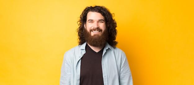 Портрет улыбающегося молодого бородатого мужчины с длинными вьющимися волосами, смотрящего в камеру на желтом фоне