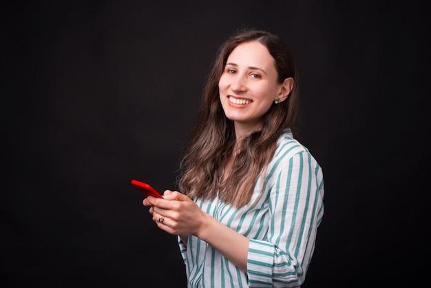 Портрет улыбающегося молодая красивая женщина, используя ее смартфон