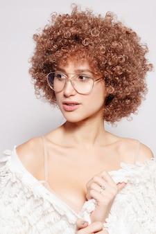 笑顔の若い黒人女性の肖像画。アフリカ系アメリカ人のアフロヘアカットとグラマーメイクの美しい若い女性の肖像画。スタジオショット。眼鏡をかけている魅力的な女の子。