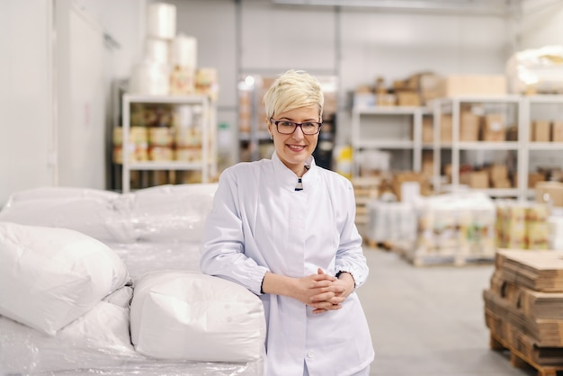 Портрет улыбается молодая блондинка кавказских блондинка в стерильной форме и очки, опираясь на мешки муки в пищевой фабрике.