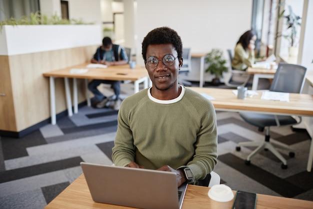 オフィスの机でラップトップで作業し、エマイに答える眼鏡で笑顔の青年実業家の肖像画...