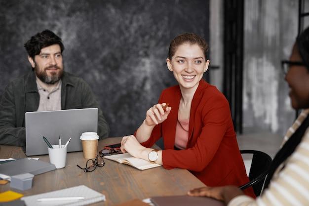 Портрет улыбающейся молодой бизнес-леди в красной куртке во время встречи с коллегами в офисе, копией пространства