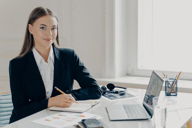 Портрет улыбающейся молодой кавказской деловой женщины в черном формальном костюме, смотрящей в камеру, сидя за большим белым столом с записной книжкой и ноутбуком, окном в светлом минималистичном фоне.