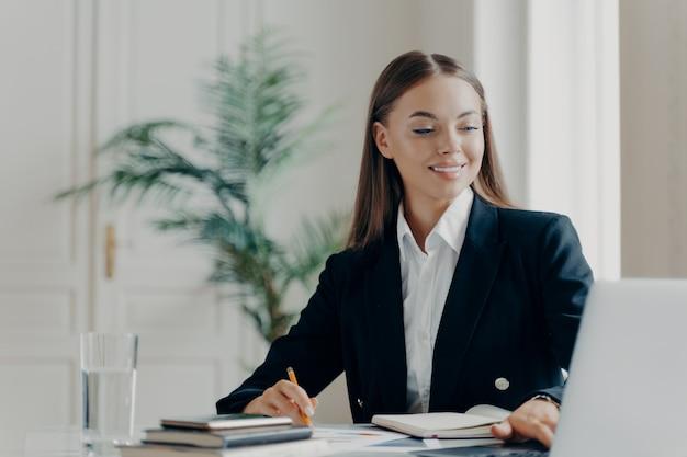 Портрет улыбающейся молодой кавказской деловой женщины в черном формальном костюме, сидящей за большим белым столом, работающим с ноутбуком и записывающим вещи с размытым светлым фоном. люди на работе концепции
