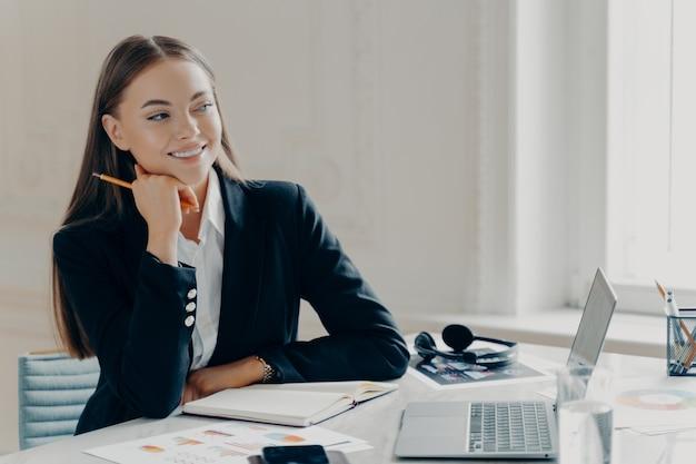 Портрет улыбающейся молодой кавказской деловой женщины в черном формальном костюме, думающей и отдыхающей с головой, сидя за большим белым столом с ноутбуком и ноутбуком, окном в светлом минималистичном фоне.